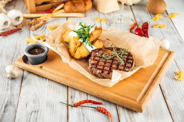 Стейк из ковбойской говядины с печеным картофелем и сметаной