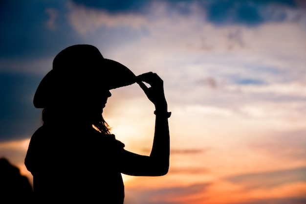 Cowboy girl silhouette on sunset