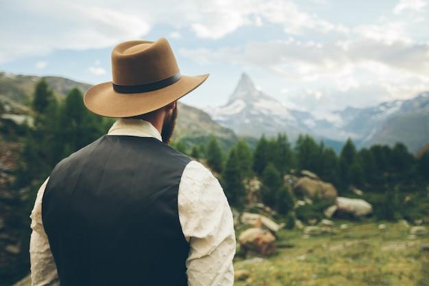 Cowboy man hiking to matterhorn mountain in summer in switzerland