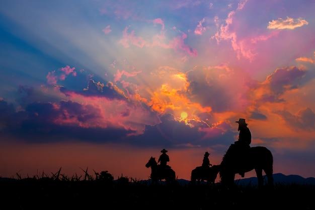 산과 일몰 하늘의 전망과 말을 타고 카우보이.