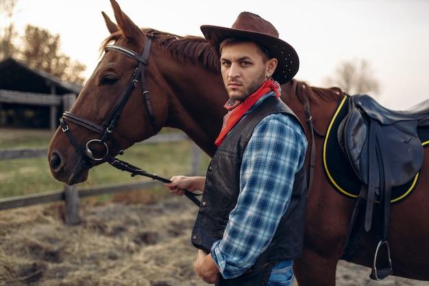 Ковбой позирует с лошадью на ранчо в техасе, дикий запад