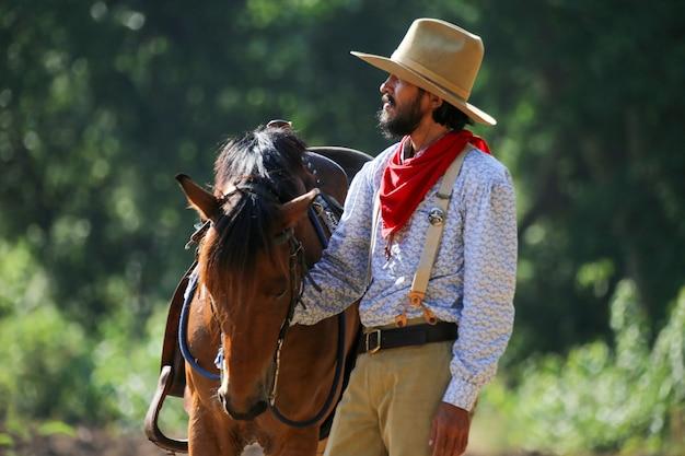 森に対して湖で馬に乗るカウボーイ