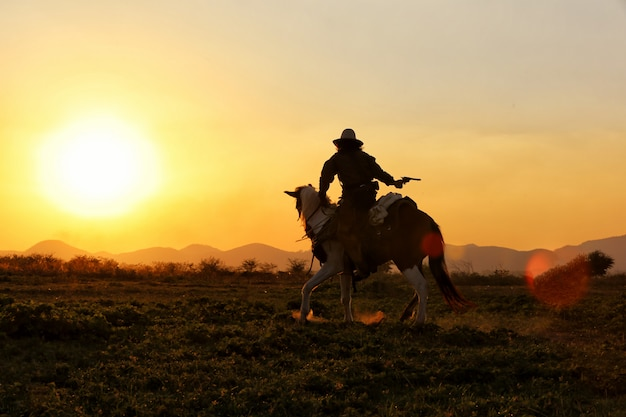 Cowboy riding horses in the field against sunset