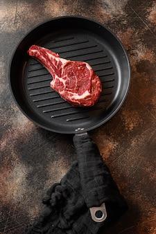 Ковбойский стейк на сковороде для гриля или сырой стейк томагавк, вид сверху