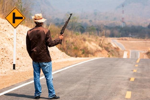 美しい山々を通してタイの田舎の美しい道に銃を持つカウボーイ