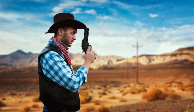 Cowboy with revolver prepares to gunfight in gesert valley, western. vintage male person with gun, wild west lifestyle
