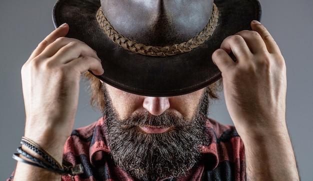 모자에 카우보이입니다. 잘생긴 수염 사나이. 면도하지 않은 카우보이 남자. 아메리칸 카우보이. 가죽 카우보이 모자. 카우보이 모자를 쓰고 젊은 남자의 초상화입니다. 프리미엄 사진