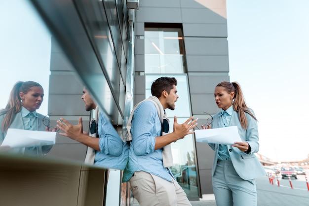 屋外で立ちながら新しいプロジェクトについて議論している同僚。書類を保持している女性。