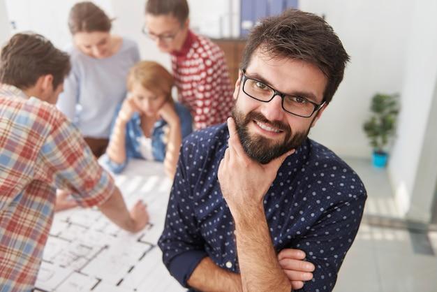 建築計画とコンピューターを持っているオフィスの同僚。マネージャーのコンセプト