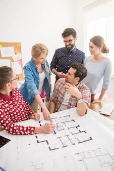 건축 계획과 컴퓨터가있는 사무실의 동료