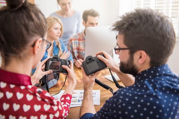 사진 카메라와 컴퓨터가있는 사무실의 동료