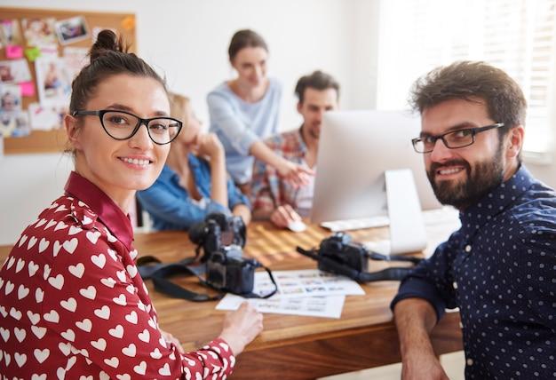 Коллеги в офисе с фотоаппаратами и компьютером