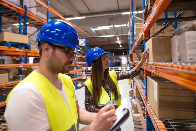 Coworkers checking inventory in large warehouse storage department