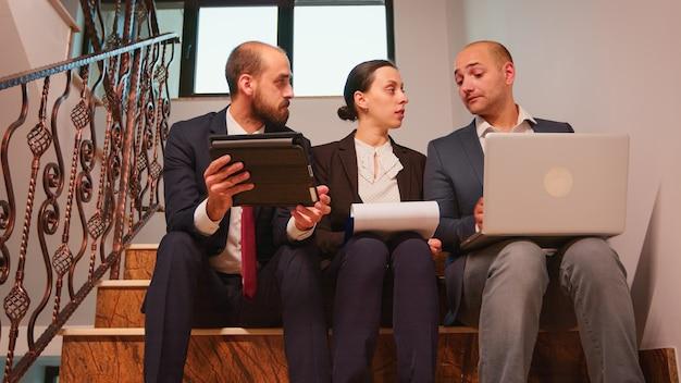 ノートパソコンとタブレットの分析レポートを使用して、オフィスビルの階段に座って難しい締め切りに取り組む計画について話し合っている同僚。階段の会社のマネージャーとオフィスエグゼクティブのグループ。