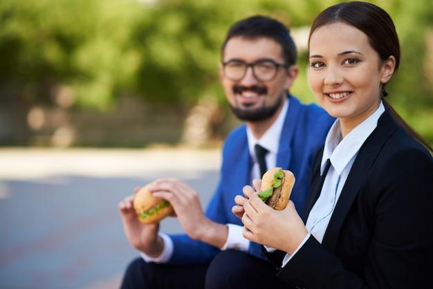 Сотрудники едят гамбургер