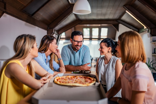 Coworkers eating pizza during work break at modern office.