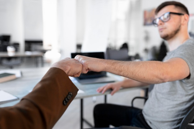 Coworkers fist bumping at the office