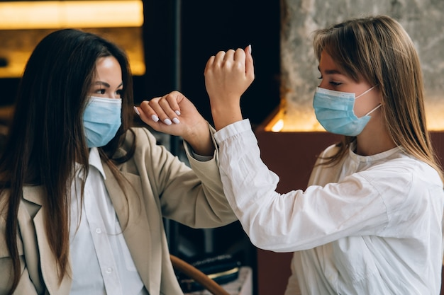 Коллеги в защитных масках дают пять локтями