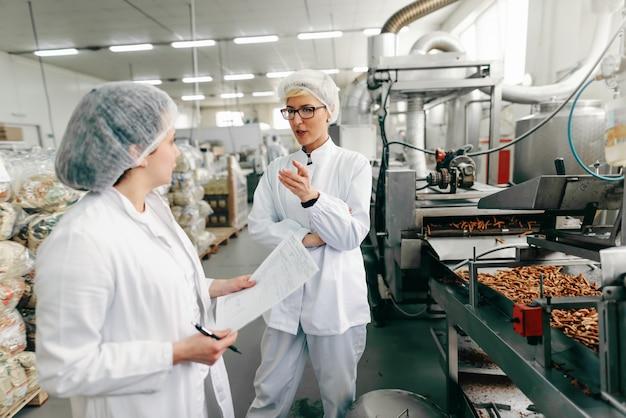 Сотрудники в белой форме и со стерильными крышками на головах обсуждают качество продукции, стоя на пищевой фабрике.