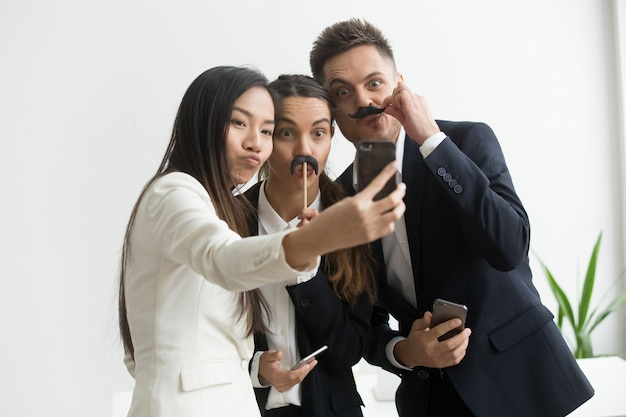 Coworkers making picture with mustache accessory