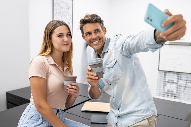 Coworkers man and woman taking selfie with smartphone and coffee
