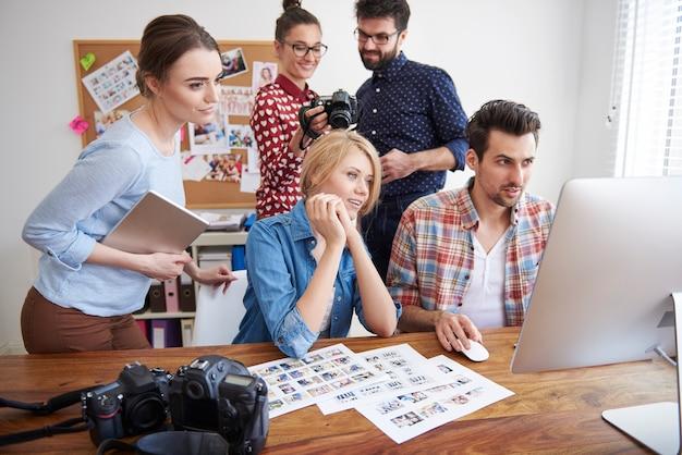 Colleghi in ufficio con macchine fotografiche e un computer