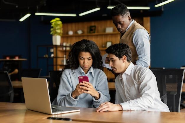 Colleghi in ufficio che lavorano con laptop e smartphone
