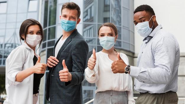 Коллеги на открытом воздухе во время пандемии в масках и поднимают вверх большие пальцы руки