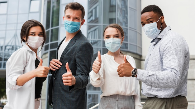 Coworkers outdoors during pandemic wearing masks and giving thumbs up