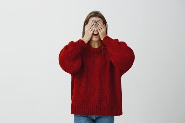 Colleghe che preparano sorpresa per la ragazza di compleanno. ritratto di bella donna caucasica matura in maglione allentato rosso, coprendo gli occhi con i palmi delle mani e aprendo la bocca, aspettando l'essenza o giocando a nascondino