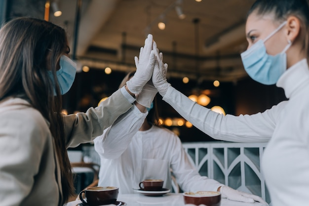 Coworkers in protective masks give a high five in the office
