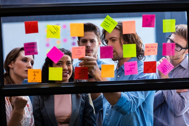 Coworkers reading a post it on a window