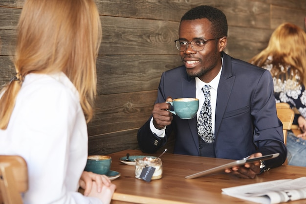 Coworkers sitting in cafe dressed formally