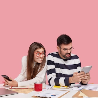 Coworkers sitting at desk with documents and gadgets