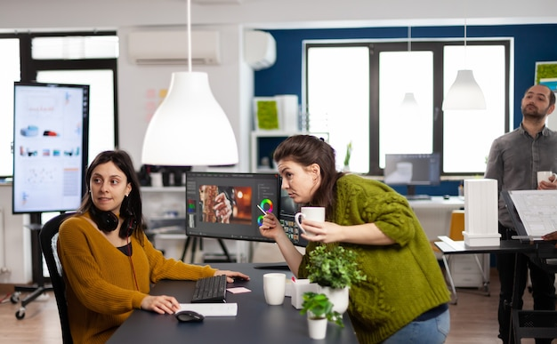 Coworkers talking about movie project looking at film footage working in creative start up agency office with two monitors