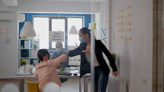 コロナウイルスの感染を避けるために肘に触れる同僚、社会的距離を尊重する会社のプロジェクトに取り組んでいるテーブルの机に座っている間、医療用フェイスマスクを着用しているビジネスチーム