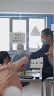 의료용 얼굴 마스크를 착용 한 코로나 바이러스 비즈니스 팀의 감염을 피하기 위해 팔꿈치를 만지는 동료.