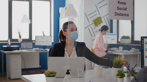 Coworkers wearing protective face mask maintaining social distancing to avoid infection with coronavirus, while working at management company statistics in new normal business office.