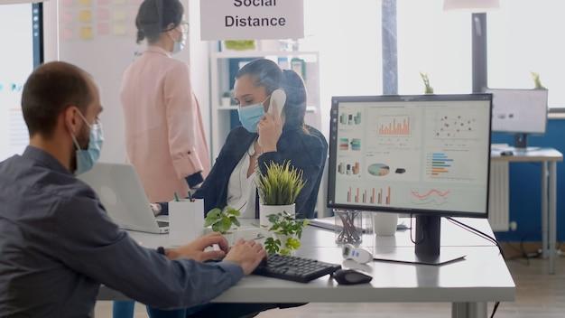 ラップトップコンピューターで作業している新しい通常の会社のオフィスの机に座って、コロナウイルスのパンデミック中に電話で話しているフェイスマスクを持った同僚。チームはウイルス病を回避するために社会的距離を維持します