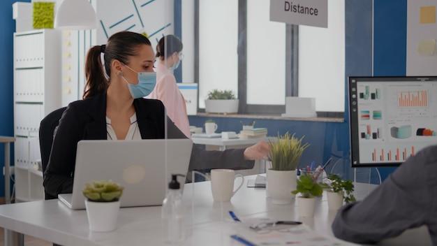 コロナウイルスの世界的大流行の間、新しい通常のオフィスで一緒に働く保護フェイスマスクを持つ同僚。社会的距離を維持しながらビジネスレポートをチェックするチーム