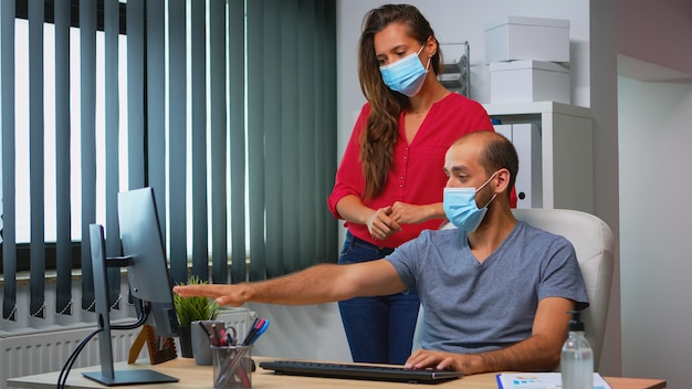 Coworkers with protection face masks working together in workplace during pandemic. team in new normal office workspace in personal corporate company typing on computer keyboard looking at desktop