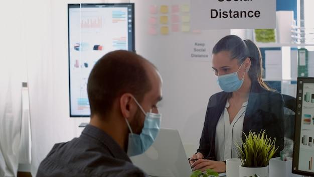 世界的な流行の間にコロナウイルスの感染を避けるために保護フェイスマスクを身に着けているビジネスアイデアで働いている同僚。コンピューターチェック担当者に入力している間、社会的距離を保つ同僚