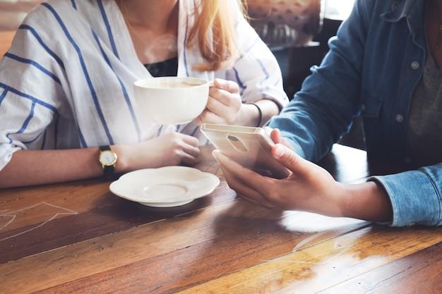 スマートフォンでカフェで働く同僚