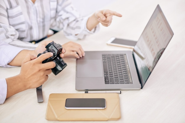 Coworking photographers with gadget at desk