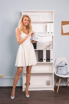 コワーキングスペース、フリーランス、人々のコンセプト-段ボール箱を持っている金髪の若い女性