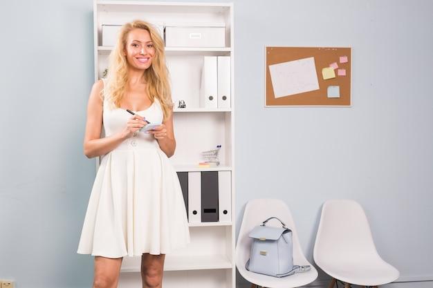 コワーキングスペース、フリーランス、人々のコンセプト-チケットに何かを書いている金髪の若い女性。
