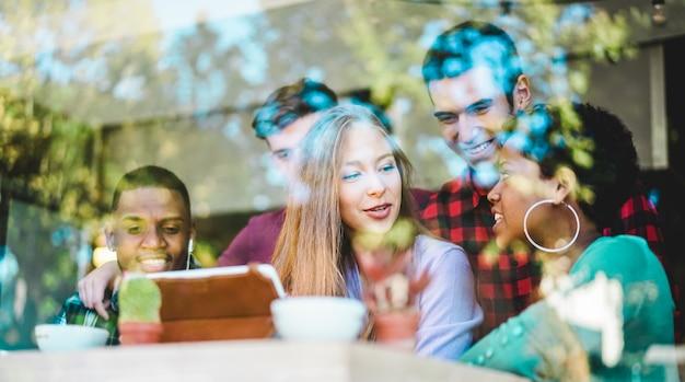 Счастливые друзья смотря видео на планшете внутри coworking интернет-бара. молодые люди миллениума развлекаются с технологическими тенденциями в интернет-кафе