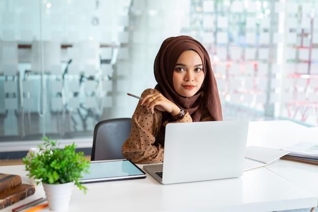 Молодая азиатская мусульманская бизнес-леди в умной вскользь носке, деле и усмехаться пока сидящ в творческом coworking.