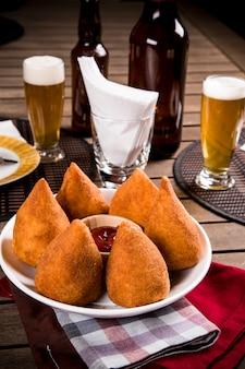 Коксинья, бразильская закуска, на фоне бара.
