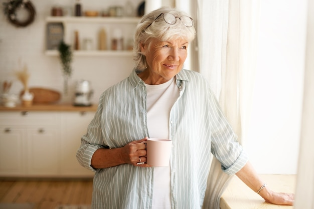 居心地のよさ、家庭性、レジャーのコンセプト。朝のコーヒーを楽しんだり、マグカップを持って、窓ガラスを通して外を見て、頭に丸い眼鏡をかけたスタイリッシュな白髪の女性の肖像画